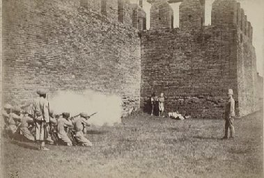 A British firing squad executes Burmese 'rebels' outside the walls of Mandalay.