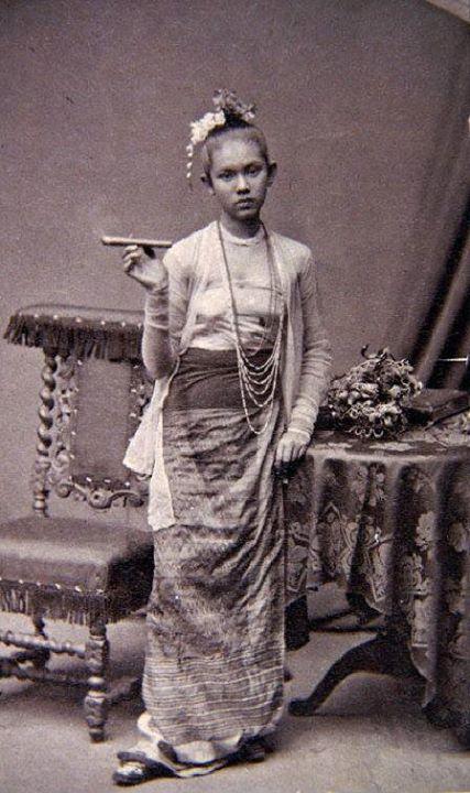 """၁၈၇၅ ခုနှစ်ဝန်းကျင်က ဂျာမန်လူမျိုး မျိုးနွယ်လေ့လာသူနှင့် ရှာဖွေစူးစမ်းသူ ဖီဒါဂျဂါ (Fedor Jagor) က ဘာလင်ရှိ ပြတိုက်များတွင် ထားရန် ရန်ကုန်သို့ လာရောက် ရိုက်ကူးသွားသော """"Frau mit Zigarre"""""""